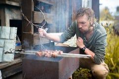 En man steker kebaber på Mongal i hans trädgårds- täppa royaltyfri fotografi