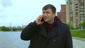 En man talar på en mobiltelefon mot bakgrunden av en cityscape stock video