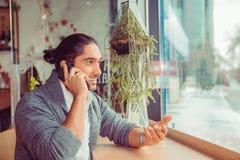 En man talar på telefonen och le arkivfoton