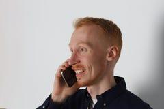En man talar på telefonen och ler på arbete Vit bakgrund Bekläda beskådar Royaltyfria Foton