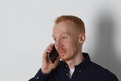 En man talar på telefonen och ler på arbete Vit bakgrund Bekläda beskådar Arkivbild