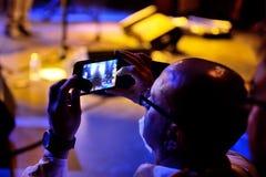 En man tar en bild med hans smartphone i en konsert på den Luz de Gas klubban Royaltyfria Foton