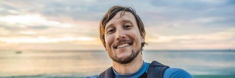 En man tar en selfie på bakgrunden av havet och solnedgångBANRET, LÅNGT FORMAT royaltyfri foto