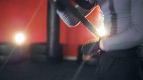 En man tejpar hans egna händer med en svart boxningsjal lager videofilmer