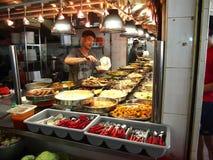 En man tjänar som mat för en kund på en gatuförsäljare i staden av Tampines i Singapore Royaltyfri Fotografi