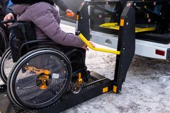 En man trycker på en knapp på kontrollbordet för att välja upp en kvinna i en rullstol i en taxi för handikappade personer Specia arkivfoton