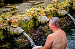 En man tvättades hans kropp på templet för Bali den heliga vårvatten Arkivbild