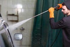 En man tvättar en bil med en rubber slang arkivfoton
