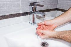 En man tvättar hans händer i badrummet Royaltyfri Foto