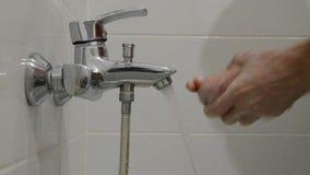 En man tvättar hans händer med tvål under klappet med rent vatten lager videofilmer