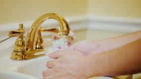 En man tvättar hans händer under ett förgyllt klapp lager videofilmer