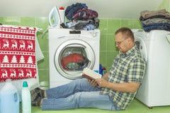 En man tvättar kläder i tvagningmaskinen Hushållsarbetemän Man som hjälper hans fru, när tvätta kläder Arkivfoto