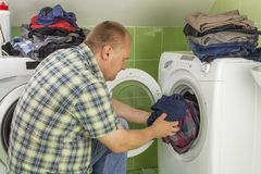 En man tvättar kläder i tvagningmaskinen Hushållsarbetemän Man som hjälper hans fru, när tvätta kläder Fotografering för Bildbyråer