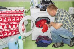 En man tvättar kläder i tvagningmaskinen Hushållsarbetemän Man som hjälper hans fru, när tvätta kläder Royaltyfri Bild