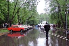 En man under paraplyet ser gamla bilar Arkivfoton
