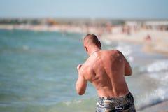 En man utbildar på stranden Fotografering för Bildbyråer