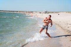 En man utbildar på stranden Royaltyfri Foto