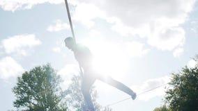 En man utför trick med ett polanseende på en kabel ovanför jordningen Mycket kalla trick arkivfilmer