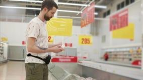 En man väljer djupfryst kött stock video
