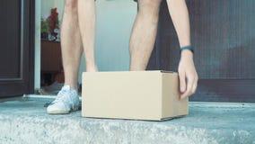 En man väljer upp en packe utifrån hans ytterdörr lager videofilmer