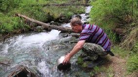 En man väljer upp vatten från en bergflod arkivfilmer