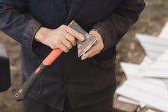 En man vässar en blyertspenna med en yxa royaltyfri fotografi