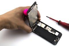 En man var repairmanen som He förbereder sig att reparera det mobiltelefonändringsskärmen och fallet Arkivbild
