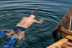 En man - en vintersimmare som simmar i vinterh?let royaltyfri bild