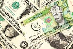 En manat från Turkmenistan med amerikanen en dollar räkningar arkivbild