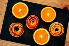 En mandarin tjänas som på en mörk sten med en dekor av skalar citruns arkivfoto