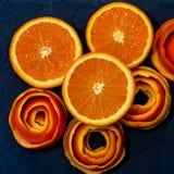 En mandarin tj?nas som p? en m?rk sten med en dekor av skalar citruns En halv tangerin arkivbilder