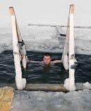 En mandykning i is-spela golfboll i hål på laken i vinter Arkivbild