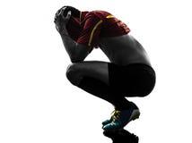 En manfotbollspelare som lossar förtvivlankonturn Arkivfoton