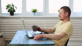 En manfreelancer arbetar avlägset hemma på en bärbar dator och meddelar med kollegor i en video pratstund lager videofilmer