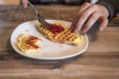 En mangeant les gaufres faites maison du plat blanc avec de la confiture de fraise rouge gelez Images stock