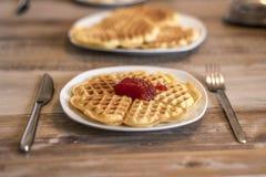 En mangeant les gaufres faites maison du plat blanc avec de la confiture de fraise rouge gelez Photographie stock