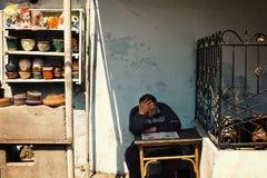 en mankeramiker som läser en tidning på ett skrivbord, medan vänta på kunder för hans produkter royaltyfri foto