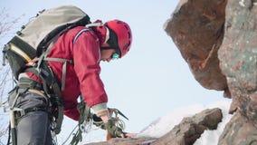 En manklättrare i en röd dräkt och utrustning, på hans knä, klättrar berget som lutar på en isyxa stock video