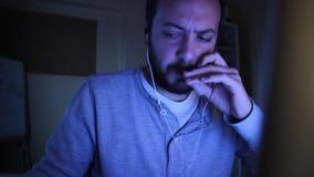 En manläsning/sökande något på bärbara datorn och än röker han en cigarett stock video