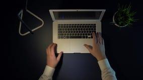 En manlig affärsman vänder på en bärbar dator, sätter på hans exponeringsglas och startar hans arbetsdag som sitter på tabellen arkivfilmer