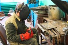 En manlig arbetare en welder i en skyddande maskering svetsar ett metallrör på en svetsningstation i ett seminarium på en metallu arkivfoton