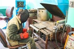 En manlig arbetare en welder i en skyddande maskering svetsar ett metallrör på en svetsningstation i ett seminarium på en metallu royaltyfri foto