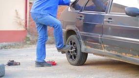 En manlig automatisk mekaniker fäller ned bilen till jordningen och fixar hjulet på axeln av bilen Tid varvar arkivfilmer