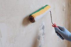 En manlig blått-behandskad hand grundade en betongvägg med en rulle Begreppet av den hem- reparationen, avslutande arbeten som fö arkivbild