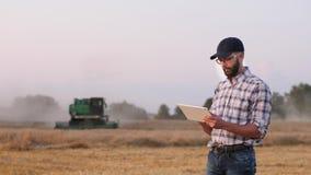 En manlig bonde använder en digital minnestavla i fältet stock video