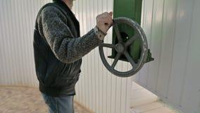 En manlig forskare roterar det manuella hjulet av den öppnande mekanismen av kupoldörrarna av en sol- observatorium vetenskapligt lager videofilmer