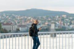 En manlig gångare som waling på en bro som ser hans mobiltelefon Royaltyfria Foton