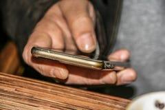 En manlig hand rymmer en mobiltelefon Arkivfoton