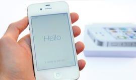 En manlig hand som rymmer en vit Apple Iphone apparat över och ett Iphone fall på bakgrunden som isoleras i vit bakgrund Royaltyfri Bild