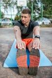 En manlig idrottsman nen som gör gymnastik som sträcker muskler, utbildande muskelböjlighetsplasticitet på mattt, i ny luft för s fotografering för bildbyråer
